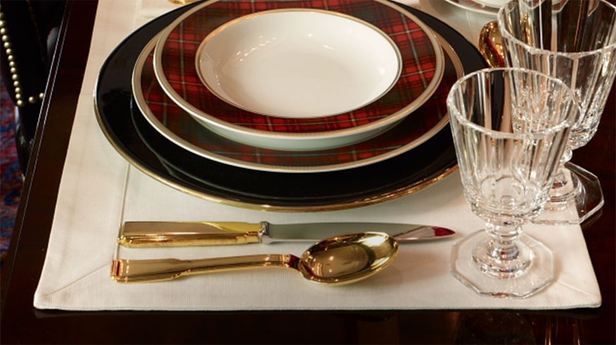 Place setting with gold-toned flatware, plaid-patterned dishes & stemmed glasses