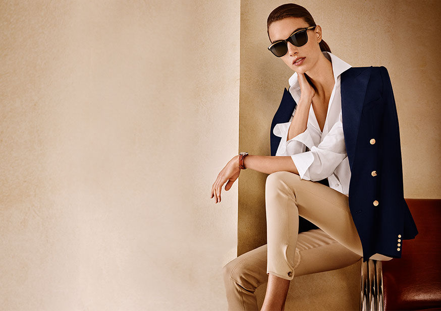 Woman wears sunglasses, crisp white shirt, and skinny pants, with navy blazer draped over her shoulders