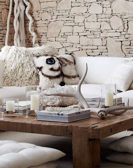 White accessories on coffee table near sofa with plush throw pillows