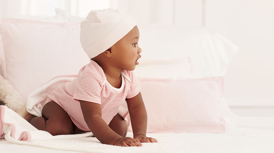 Baby wears pink striped shortall and knit hat