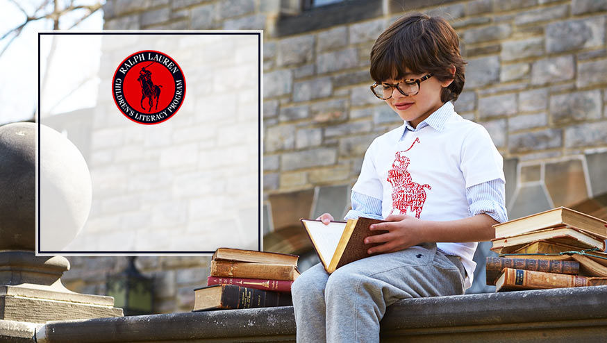 Boy wearing white Literacy tee & grey sweatpant reads book