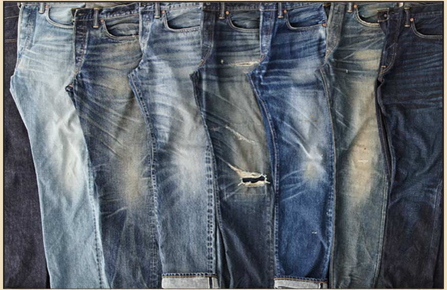 Row of folded jeans in various washes & levels of distressing