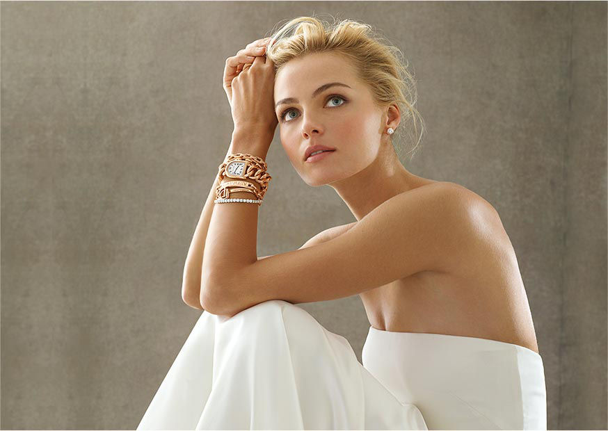 Woman in chic white strapless gown models fine jewelry from the collection