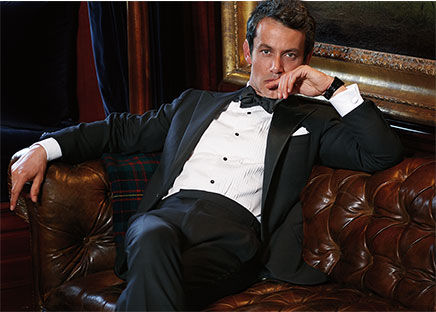 In black tuxedo, Andrew Lauren sits on leather chesterfield sofa