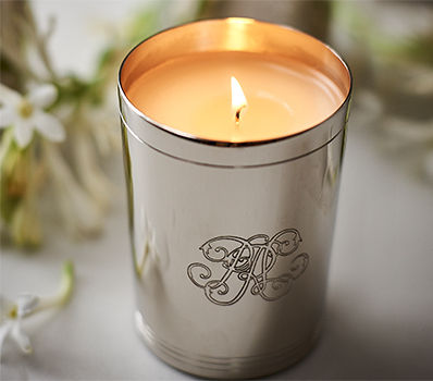 Lit candle in silver holder with script RL engraving
